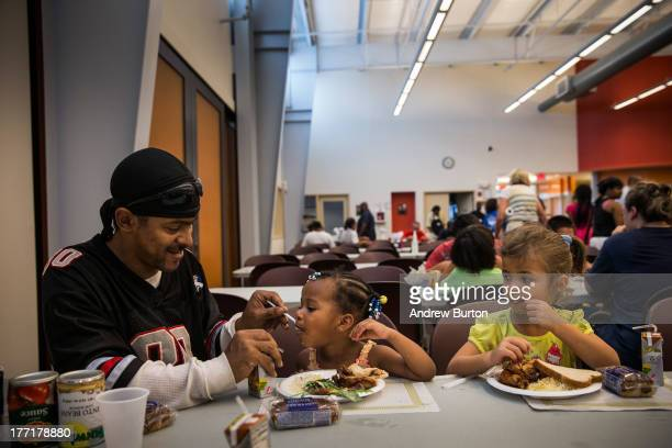 LeManuel Farrish helps his cousin Makayla Farrish age three finish her dinner at Catherdral Kitchen on August 21 2013 in Camden New Jersey Cathedral...