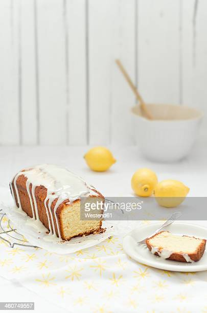 Lemon cake on cooling rack with frosting and lemon , close up