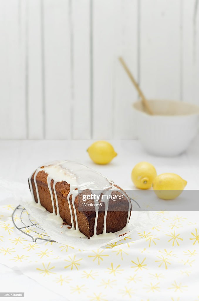 Lemon cake on cooling rack with frosting and lemon, close up
