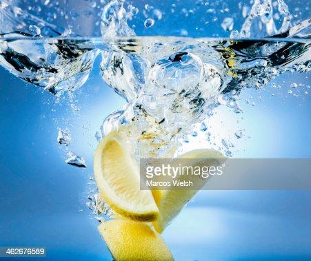 Lemon falling into water with splash
