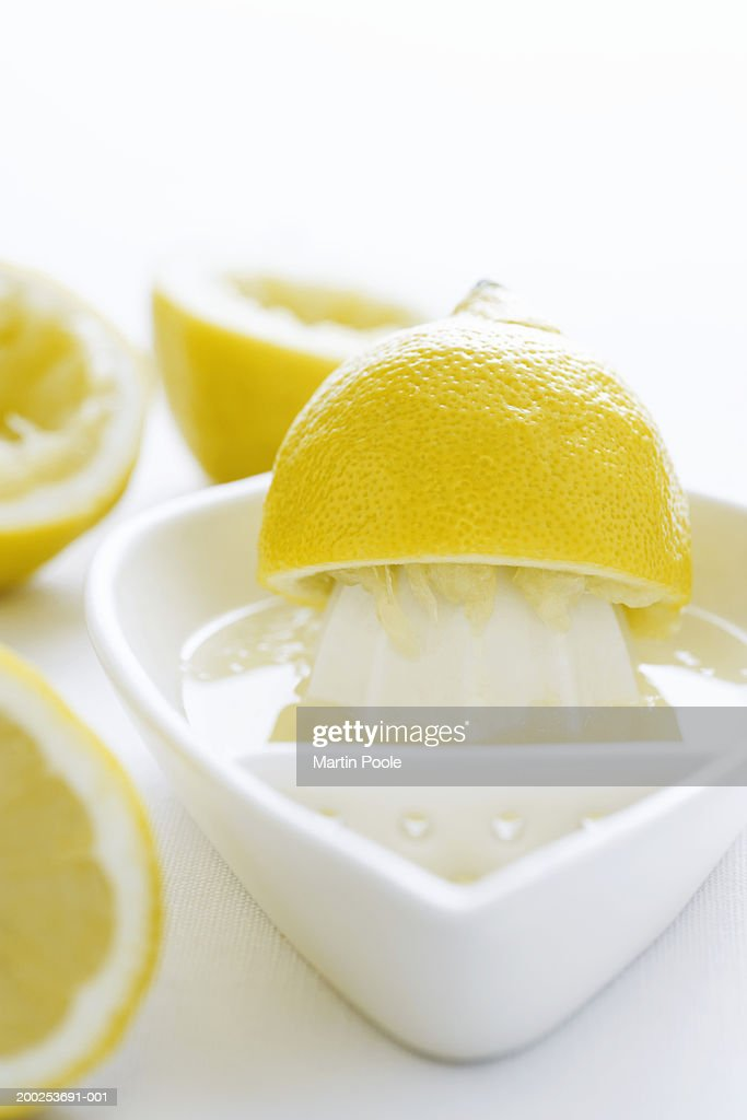 Lemon half and juice squeezer, close-up : Stock Photo