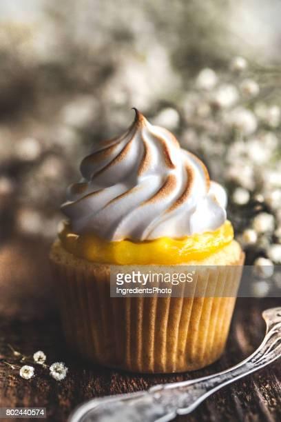 Lemon meringue cupcake on a rustic wooden table.