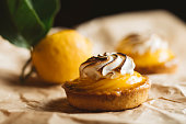 Lemon pie on the table with citrus fruits. Traditional french sweet pastry tart. Delicious, appetizing, homemade dessert with lemon cream. Copy space, closeup. Selective focus. Toned.
