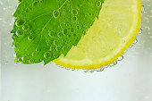 Photo of lemon slice, mint leaf and soda (water with bubbles)