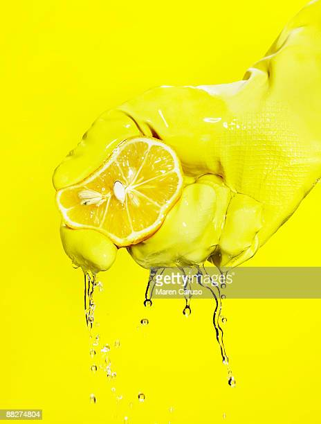 Lemon squeeze in a hand with a yellow close.
