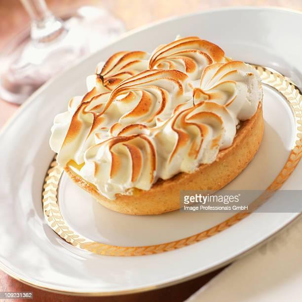 Lemon tart with baked meringue on plate