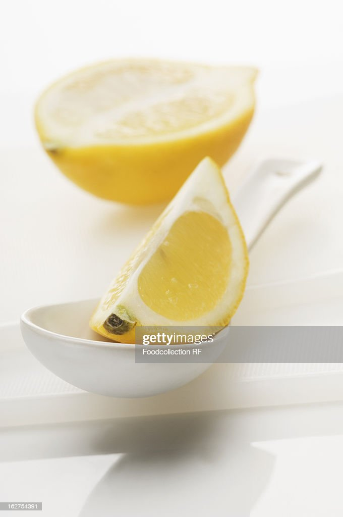 Lemon wedge on spoon with halved lemon in background : Stock Photo