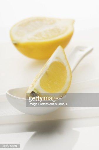 Lemon wedge on spoon with halved lemon in background : Stock Photo
