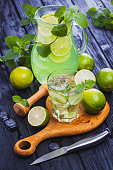 Cold refreshing summer lemonade mojito in a glass on a black wooden background