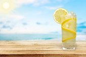 Glass of cold lemonade on wooden background
