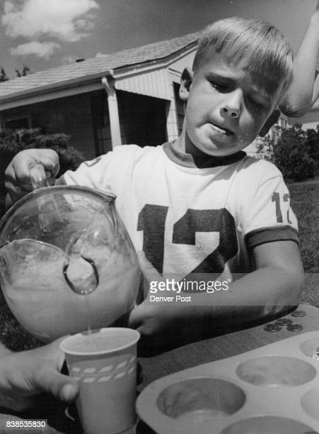Lemonade Stands Little Jim Sollenberger handles a big lemonade pitcher in filling an order for customer Kirk Smith The drinks were sold for 2 cents a...