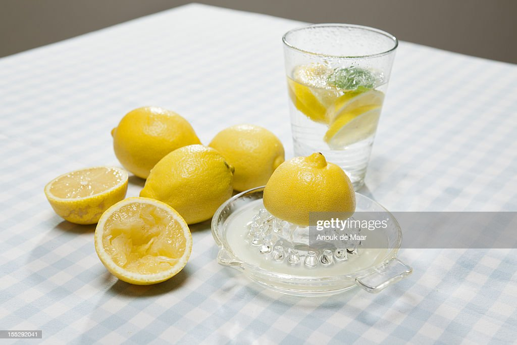Lemons, juicer and glass of water : Stock Photo
