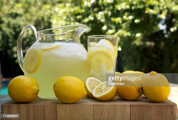 Lemons next to a pitcher and glass of fresh made lemonade