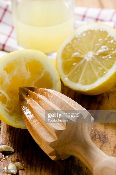 Lemons with wooden squeezer and lemon juice