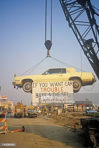 A lemonyellow Cadillac which has apparently lived up to its color hangs from a crane near a service station A sign warns future car purchasers away...