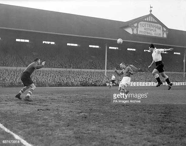 Len Dunquemin Spurs centre forward jumps high to head the ball towards the Liverpool goalkeeper Charlie Ashcroft as Ray Lambert tries to intervene