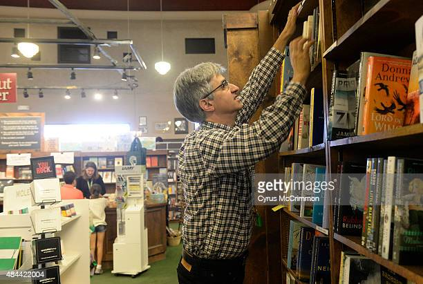 Len Vlahos organizes the bookshelves in the new fiction section as his wife Kristen Gilligan works a register in the background at left as the two...