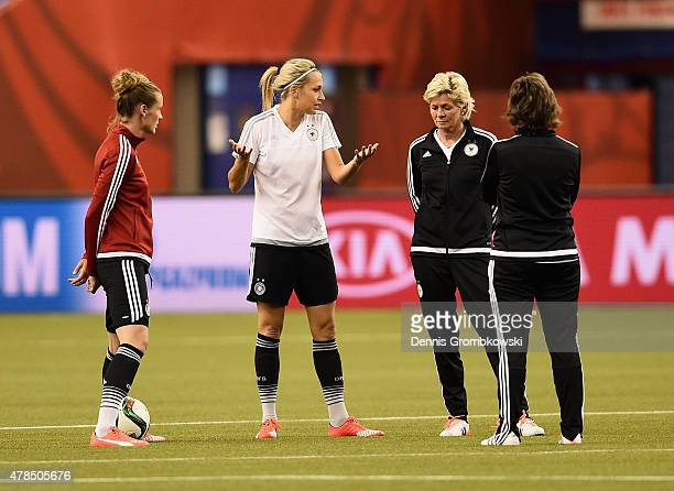 Lena Goessling of Germany exchanges words with head coach Silvia Neid during a training session at Stade Olympique de Montreal on June 25 2015 in...