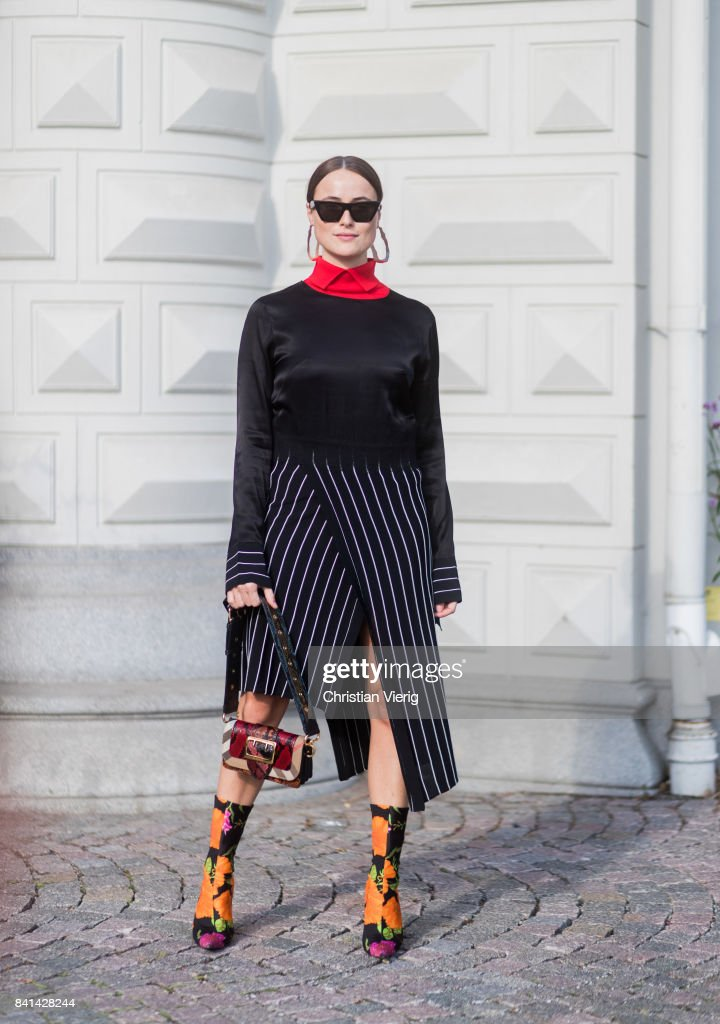 Lena Lademann wearing Balenciaga sock boots with floral print, black striped dress, knit, red turtleneck outside House of Dagmar on August 31, 2017 in Stockholm, Sweden.
