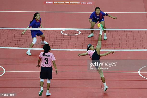 Lena Lena of Indonesia strike against Koy Xayavong and Mely Matmannivong of Laos during the Sepaktakraw Women's Double Regu during the 2013 SEA Games...