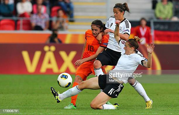 Lena Lotzen and Anja Mittag of Germany battle for the ball with Danielle van de Donk of Netherlands during the UEFA Women's Euro 2013 group B match...