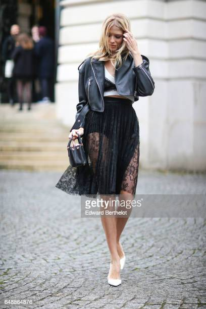 Lena Perminova wears a black leather perfecto jacket a black lace skirt and white shoes outside the Veronique Branquinho show during Paris Fashion...
