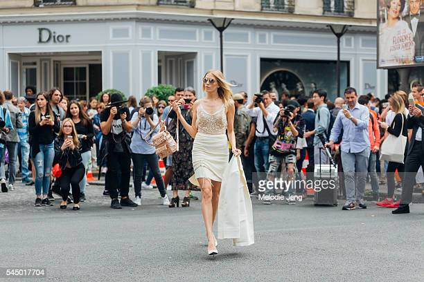 Lena Perminova wears a creamcolored Dior outfit and backpack with Linda Farrow sunglasses at the Dior show at 30 Avenue Montaigne on July 4 2016 in...