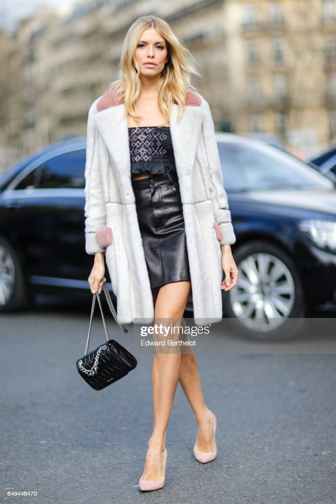 Lena Perminova wears a white coat, a black sleeveless t-shirt, a black leather skirt, pink shoes, and a black bag, outside the Miu Miu show, during Paris Fashion Week Womenswear Fall/Winter 2017/2018, on March 7, 2017 in Paris, France.