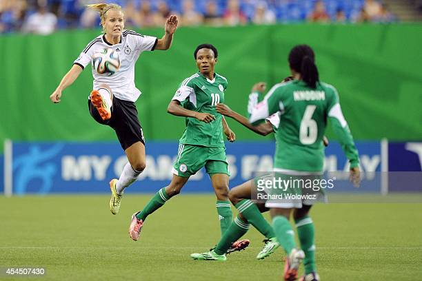 Lena Petermann of Germany jumps to kick the ball in front of Osarenoma Igbinovia and Halimatu Ayinde of Nigeria during the FIFA Women's U20 Final at...