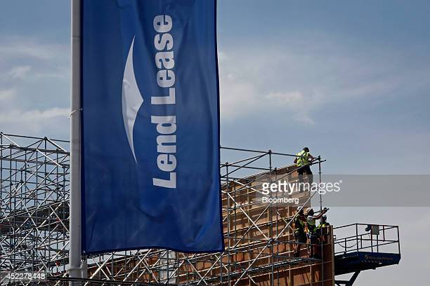 A Lend Lease logo sits on a banner as construction workers attach wooden panels to scaffolding at the designated site of the 'The International...