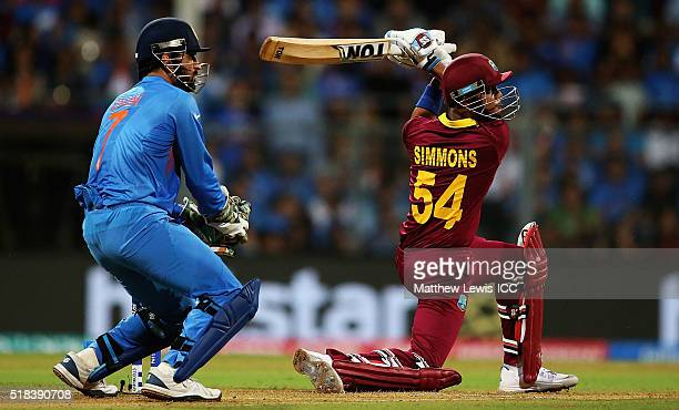 Lendl Simmons of the West Indies hits the ball towards the boundary as MS Dhoni Captain of India looks on during the ICC World Twenty20 India 2016...