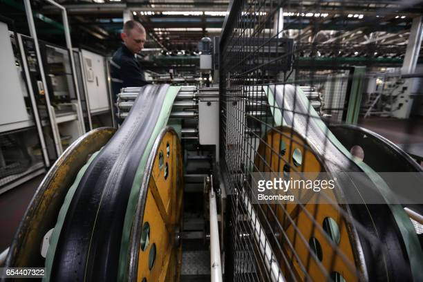 Lengths of rubber run through a tirebuilding machine before bonding to form round tires at the Belshina JSC tire factory in Babruysk Belarus on...