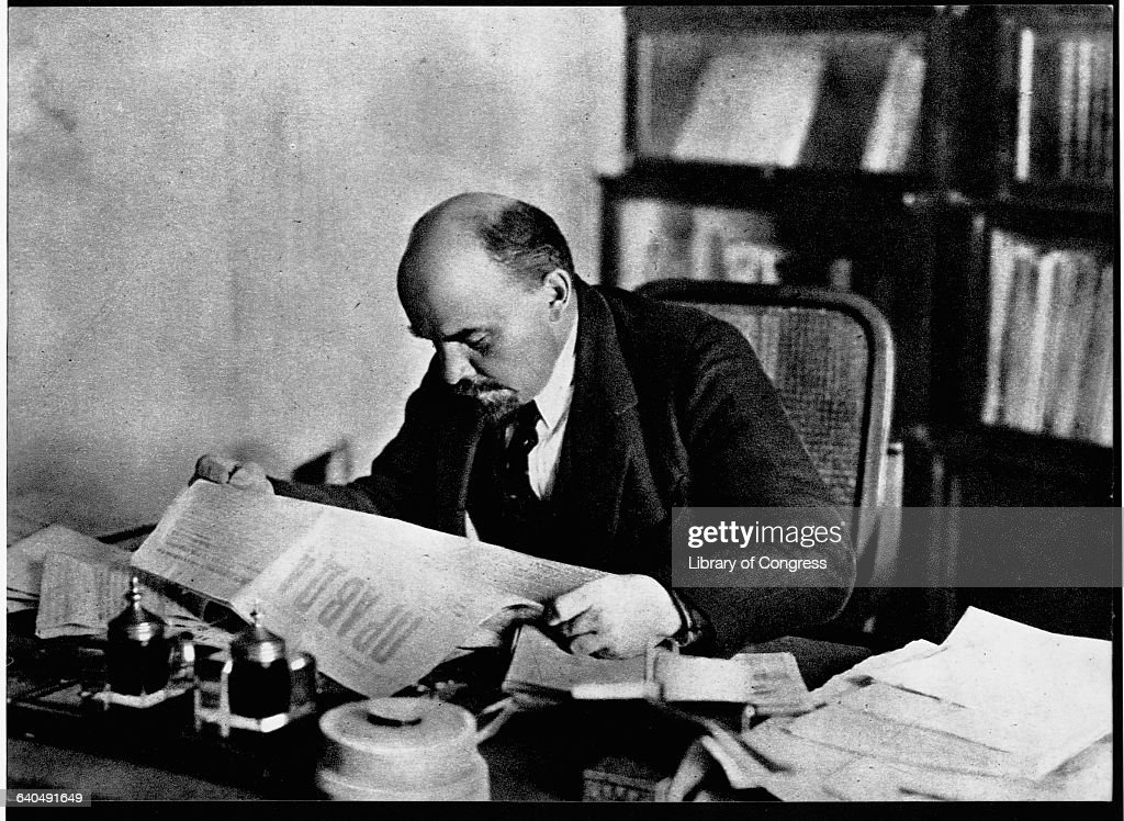 Lenin sits at his desk and reads the newspaper.