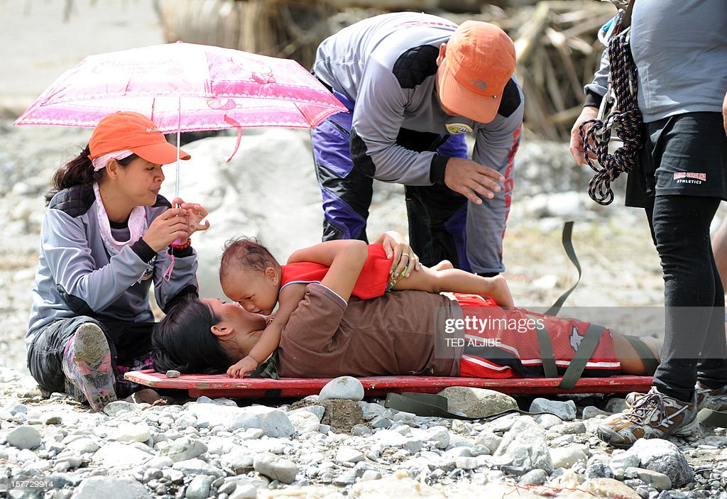Lenlen Medrano and her child (on stretcher), survivors of Typhoon Bopha, prepare to be transported across a surging river on a zip line in the town of New Bataan, compostela province on December 6, 2012. Nearly 200,000 people are homeless and more than 300 dead after the Philippines suffered its worst typhoon this year, authorities said on December 6, reaching out for international aid to cope with the scale of the disaster. AFP PHOTO / TED ALJIBE