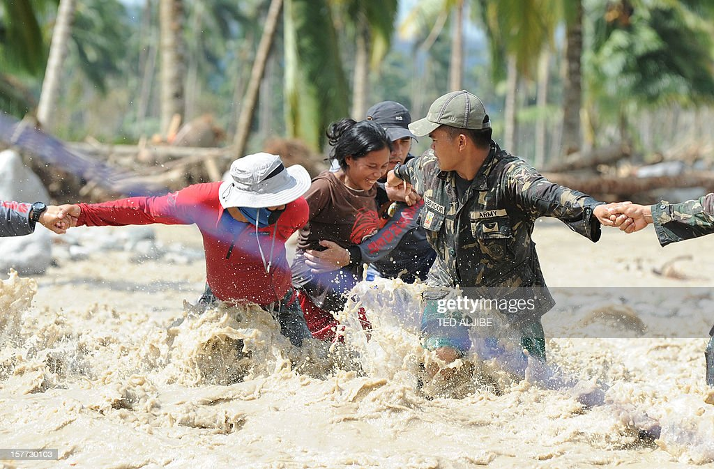 Lenlen Medrino (C) survivor of flash floods at the height of Typhoon Bopha, is helped by rescuers across a surging river in the town of New Bataan, compostela province on December 6, 2012. Nearly 200,000 people are homeless and more than 300 dead after the Philippines suffered its worst typhoon this year, authorities said on December 6, reaching out for international aid to cope with the scale of the disaster. AFP PHOTO / TED ALJIBE