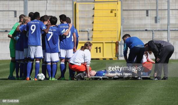 Lennart Czyborra of FC Schalke 04 lies injured on a stretcher as his team stands together during the AJuniors semi final first leg German...