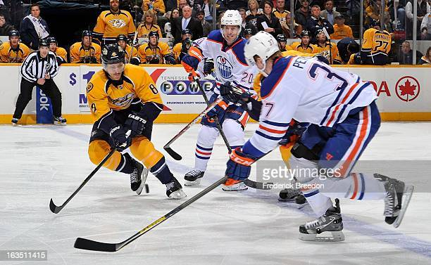 Lennart Petrell and Eric Belanger of the Edmonton Oilers plays against Kevin Klein of the Nashville Predators at Bridgestone Arena on March 8 2013 in...