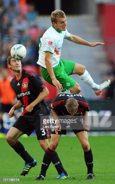 Lennart Thy of Bremen jumps over Stefan Reinartz and Lars Bender of Leverkusen during the Bundesliga match between Bayer 04 Leverkusen and SV Werder...