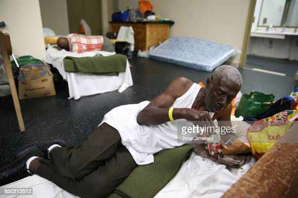 Lennox Norford from Barbuda who lost his entire home eats corned beef at a shelter in the Sir Vivian Richards Cricket Stadium on September 20 2017 in...