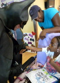 Lenny Robinson AKA 'Batman' visits with a sick child on August 16 2012 at the Rubin Institute for Advanced Orthopedics Sinai Hospital in Baltimore...