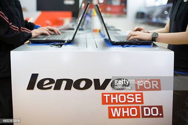 Lenovo Group Ltd signage is displayed near laptops in an arranged photograph at a Lenovo store in the Yuen Long district of Hong Kong China on Friday...