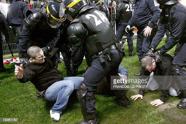 Antiriot Policemen arrest Manchester United's fans on the pitch during the Champions League football match Lille vs Manchester United at the Felix...