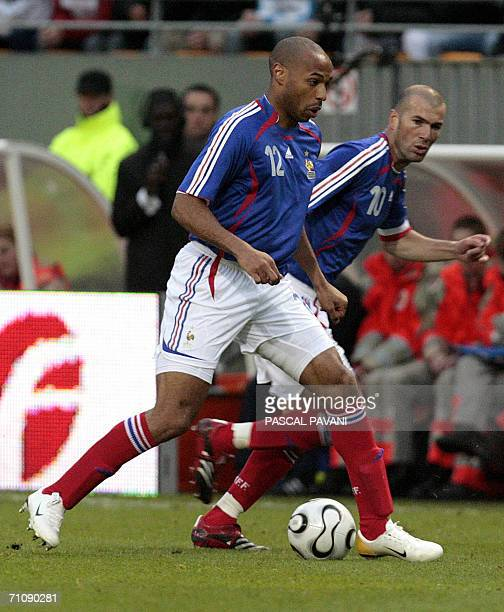 French midfielder Zinedine Zidane runs with the ball with French forward Thierry Henry during the friendly football match France vs Denmark at the...