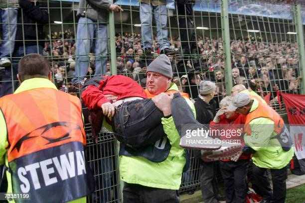 Stewarts evacuate people after clashes between Antiriot Policemen and Manchester United's fans during the Champions League football match Lille vs...