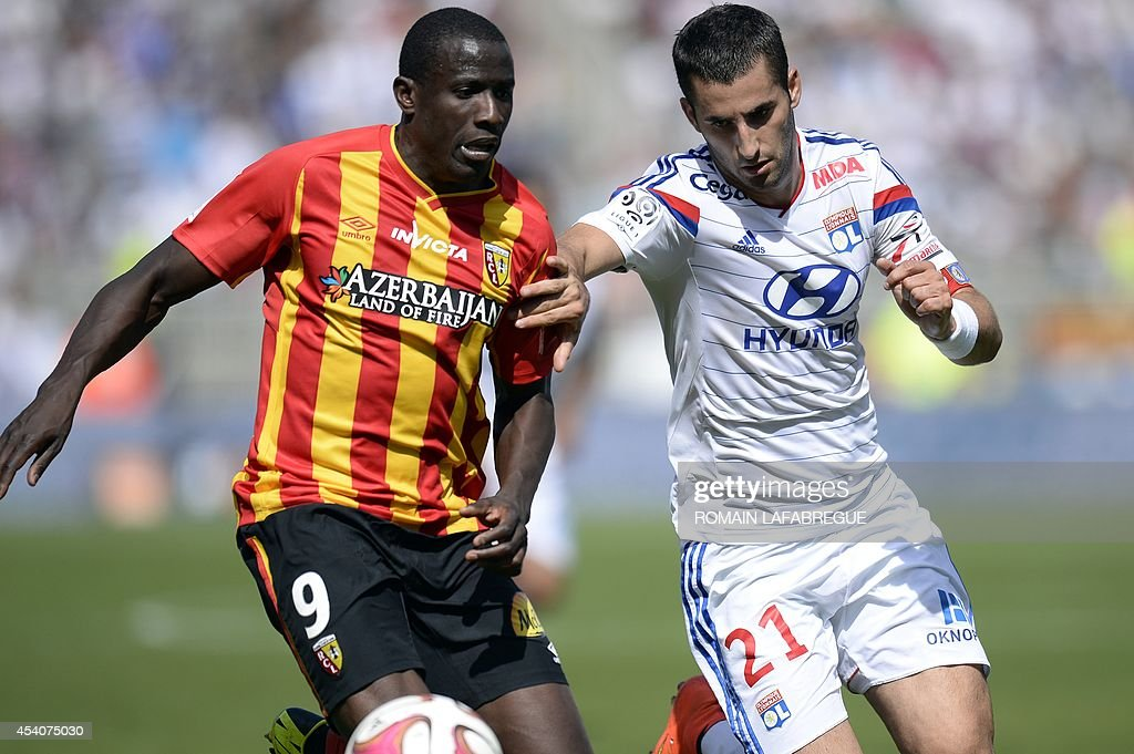 Lens' French forward Adamo Coulibaly (L) vies with Lyon's French midfielder Maxime Gonalons (R) during the French L1 football match between Lyon (OL) and Lens (RCL) at the Gerland stadium in Lyon, central-eastern France, on August 24, 2014. AFP PHOTO / ROMAIN LAFABREGUE
