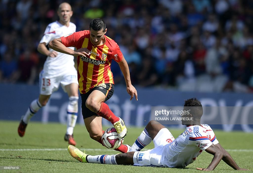 Lens' French forward Yohann Touzghar (C) is tackled by Lyon's French midfielder Arnold Mvuemba (R) during the French L1 football match between Lyon (OL) and Lens (RCL) at the Gerland stadium in Lyon, central-eastern France, on August 24, 2014. AFP PHOTO / ROMAIN LAFABREGUE