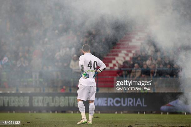 Lens' French goalkeeper Valentin Belon watches smoke spreading after fans used flares as the game is interrupted following fans misbehaviour during...