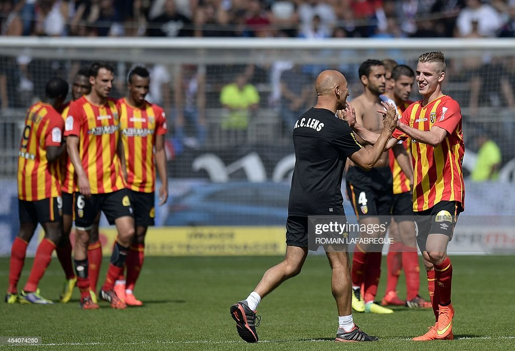 Lens' French midfielder Benjamin Bourigeaud (R) celebrates with a staff member after winning the French L1 football match between Lyon (OL) and Lens (RCL) at the Gerland stadium in Lyon, central-eastern France, on August 24, 2014. AFP PHOTO / ROMAIN LAFABREGUE