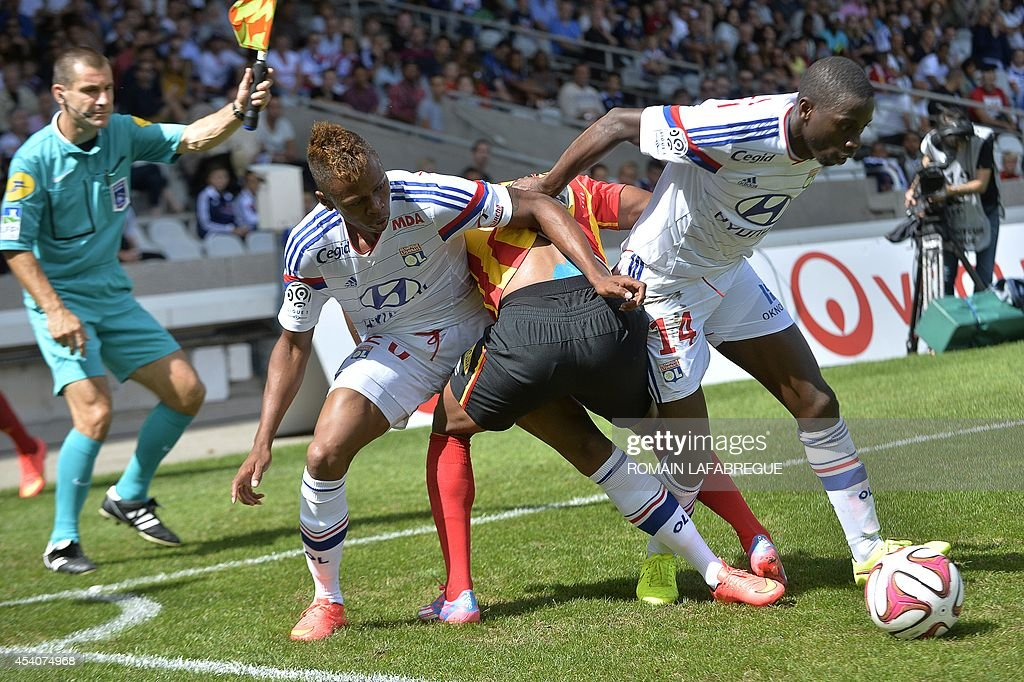 Lens' Madagascan midfielder Lalaina Nomenjanahary (C) vies for the ball with Lyon's Cameroonian forward Clinton NJie (L) and Lyon's French defender Mouhamadou Dabo (R) during the French L1 football match between Lyon (OL) and Lens (RCL) at the Gerland stadium in Lyon, central-eastern France, on August 24, 2014. AFP PHOTO / ROMAIN LAFABREGUE