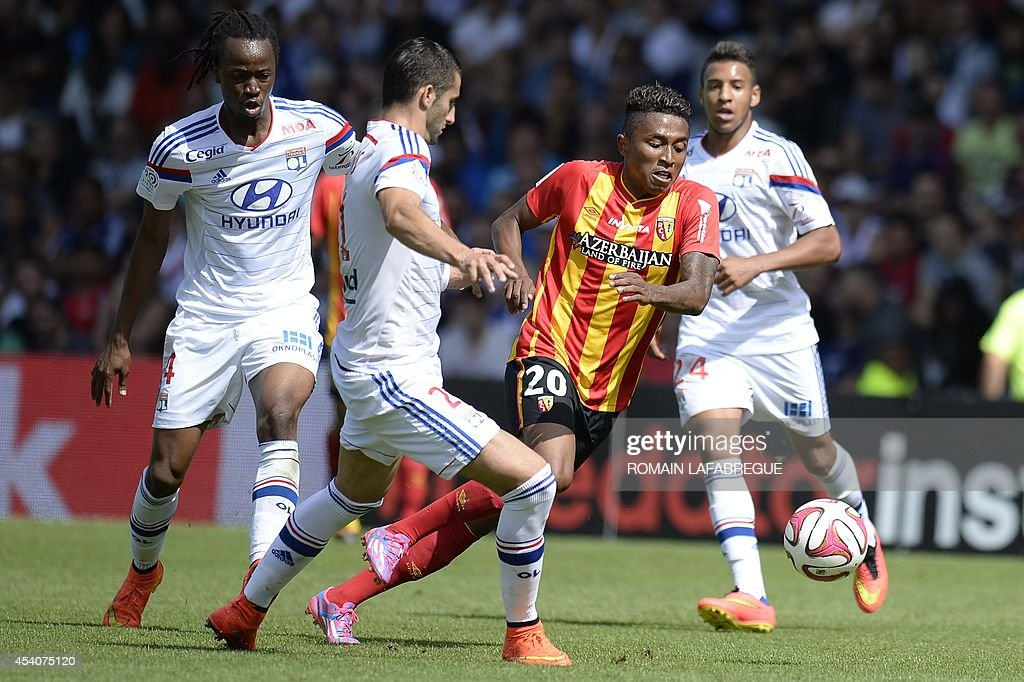 Lens' Madagascan midfielder Lalaina Nomenjanahary (2nd R) vies for the ball with Lyon's French midfielder Maxime Gonalons (2nd L) and French defender Bakary Kone (L) during the French L1 football match between Lyon (OL) and Lens (RCL) at the Gerland stadium in Lyon, central-eastern France, on August 24, 2014. AFP PHOTO / ROMAIN LAFABREGUE